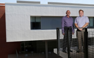 Dr. Mark Wooden (left, College of Science, Engineering and Technology) and Dr. Sherman Elliott (College of Humanities and Social Sciences) stand with the new Humanities building in the background. (Photo by Darryl Webb)