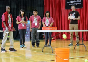 Fazille uses the Montebello team's prostetic arm to flip tennis balls into a bucket. The team's trip to the national competition in Portland, Ore., was funded by GCU.