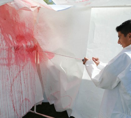 A student spurts fake blood  onto a blank canvass as part of a blood-spatter analysis demonstration at GCU's Forensic Science Day.