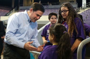 """Arizona Gov. Doug Ducey visits with Valley elementary students at GCU Arena during the 21st annual Back to School Clothing Drive """"New Clothes, New Beginnings"""" event."""