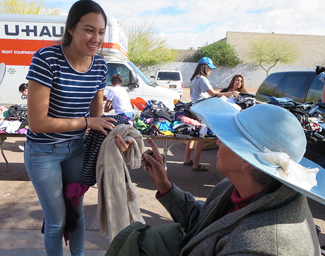 Sophomore Isabelle Cox helps Mary Mills find some clothing during a GCU Homeless Ministry event at the Central Arizona Shelter Services facility in central Phoenix.