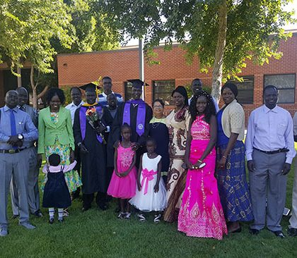 Bol Bior Kur (tallest graduate in middle) poses with his family after commencement.